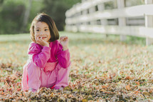 a young girl sitting in fall leaves