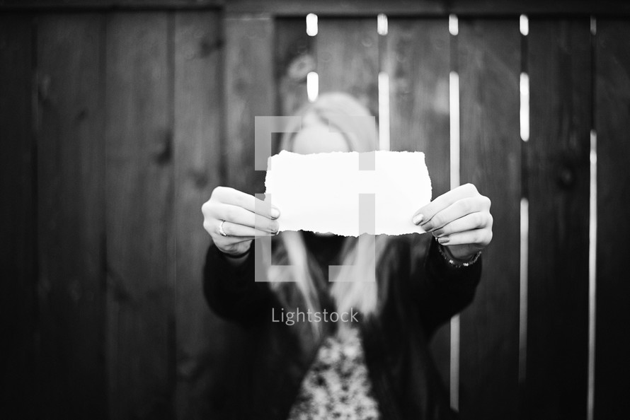 girl holding up a blank piece of paper