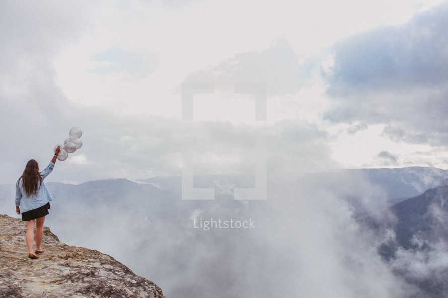 woman standing at the top of a mountain holding balloons