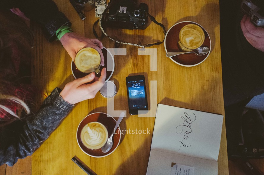 phone and camera on a table as they drink coffee