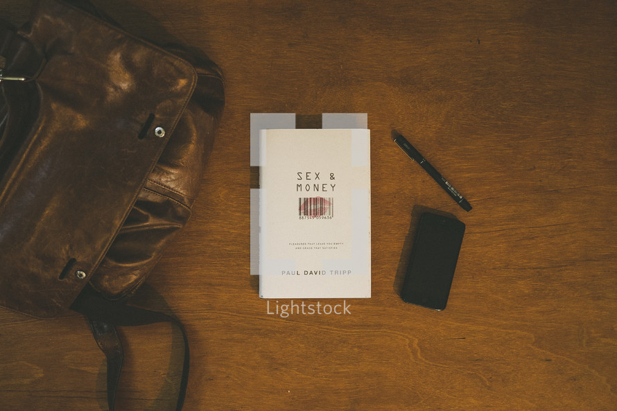 """A backpack on a table next to a book entitled, """"Sex and Money."""""""