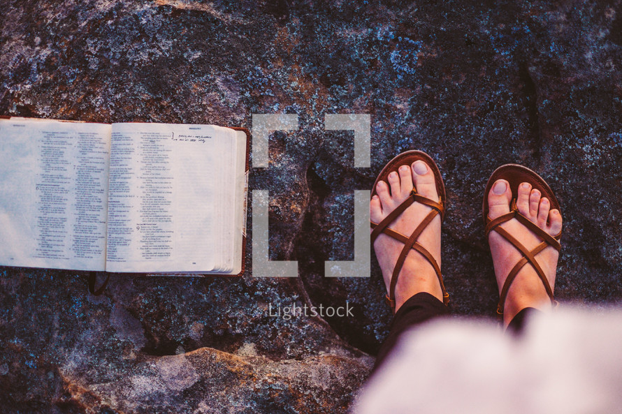 open Bible and feet in sandals