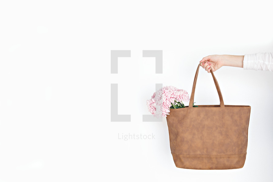 a woman carrying pink flowers in a bag