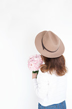 a woman in a hat holding a bouquet of pink flowers