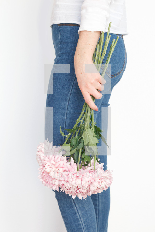 a woman holding a bouquet of flowers at her side