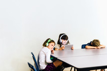 children listening to headphones and playing on tablets