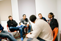 A group of young men sitting in a circle and listening to someone speaking.