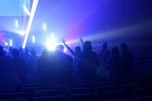 hands raised under lights at a worship service