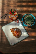 croissant and ice tea on a plate and succulent plant on a wood table