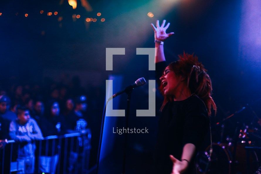 woman at a concert singing into a microphone