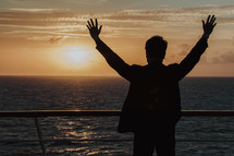man with arms raised standing on a cruise ship