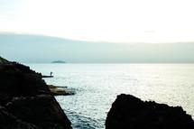 ocean view through rocks - person fishing - hills