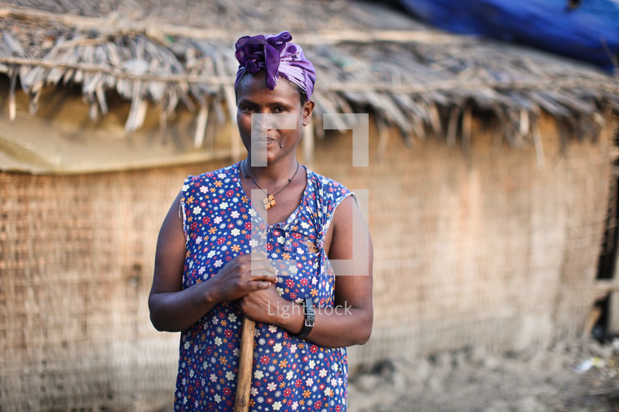 Ethiopian woman standing in front of a thatched roof house