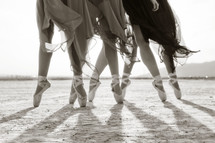 ballerinas in toe shoes dancing in the sand