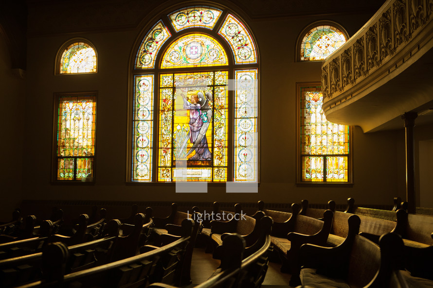 A church sanctuary with decorative stained glass windows.