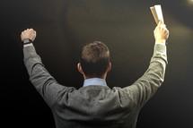 a preacher holding up a Bible during his sermon