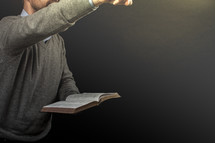 A man pointing and preaching while holding an open Bible.