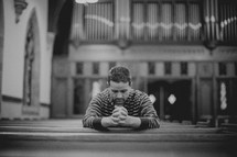 Man sitting in empty church pew praying