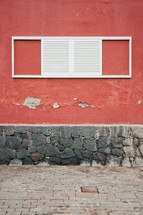 white shutters on a window on a red wall
