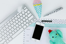 computer keyboard, ice cream cone and cactus plush toy, cellphone, planner, and pen on a desk