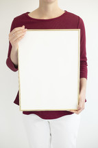 a woman holding a blank white board