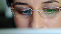 Young woman with glasses working on a digital tablet computer - close-up