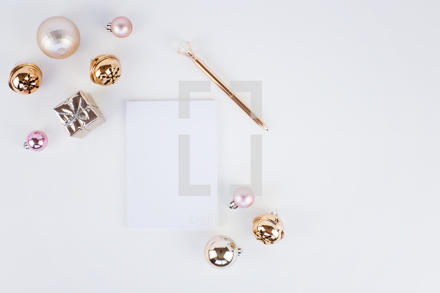 notepad, pen, and Christmas ornaments on a white background