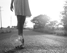 ballerina in toe shoes on a gravel road