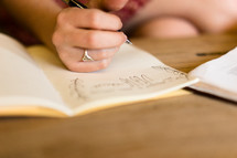 a woman writing notes in a journal while reading a Bible