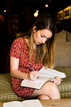 a woman reading a Bible and writing notes on the pages