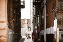 hipster bride and groom standing in an alley