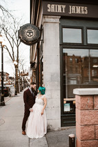 bride and groom standing on a sidewalk