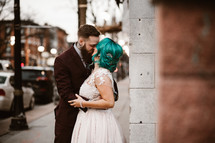 bride and groom kissing on a downtown sidewalk