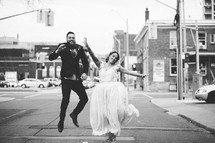 bride and groom in the middle of a street celebrating