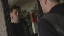 a man looking in a mirror and walking away