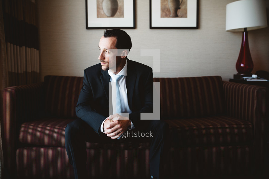 nervous groom sitting on a couch