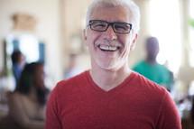 man smiling at a small group meeting