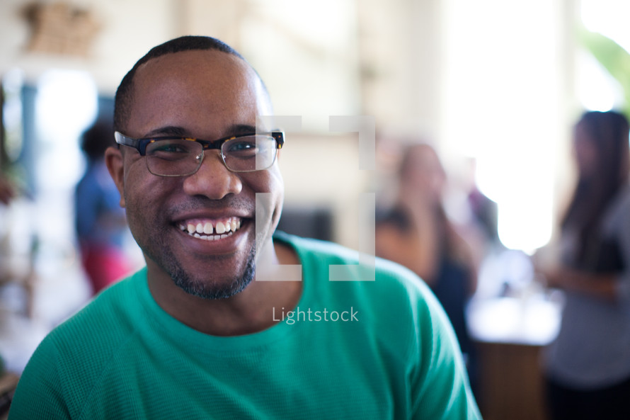 man smiling at a small group gathering