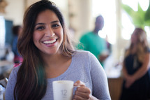woman holding a coffee mug at a small group gathering