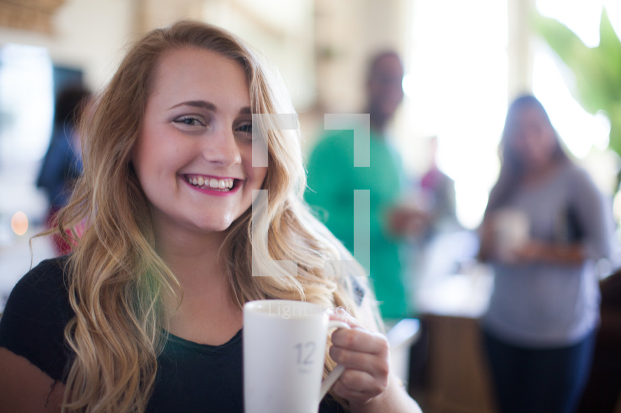 A smiling young woman holding a cup of coffee.