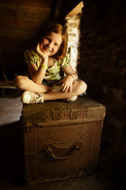 a girl sitting on an old trunk