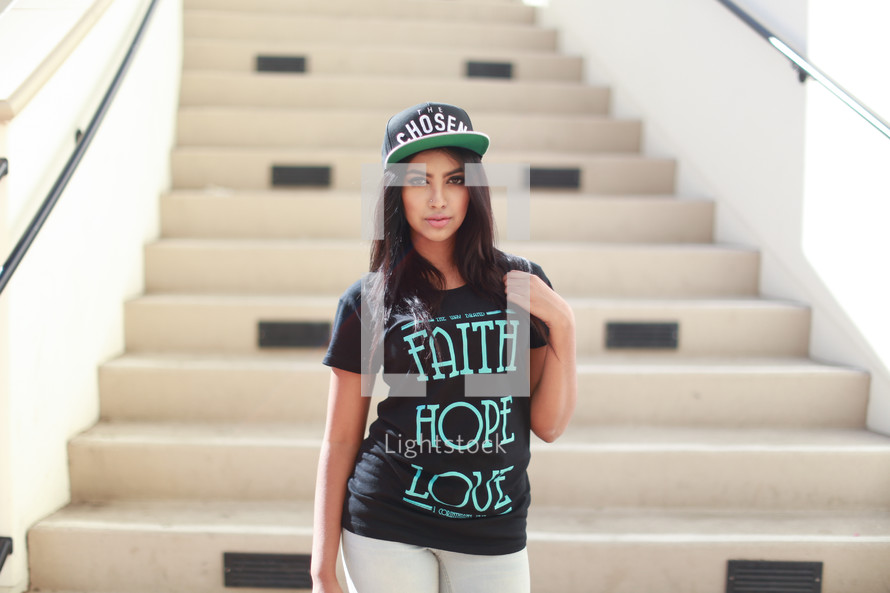 woman modeling religious t-shirts and ball cap