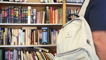 student with a book bag in a library