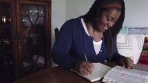 Woman sitting at a table studying the Bible, taking notes.