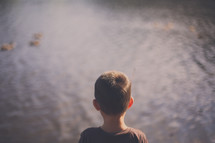 boy child looking at water in a pond