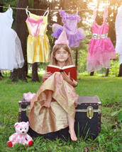 a child dressed up as a princess reading a book