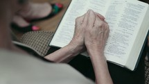 senior woman praying over a Bible