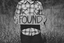 "Man holding ""Found"" cardboard sign"