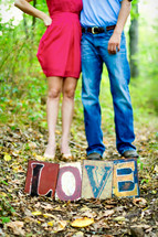 legs of a couple standing on top of the word LOVE