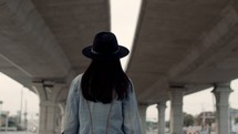 a woman walking under an overpass
